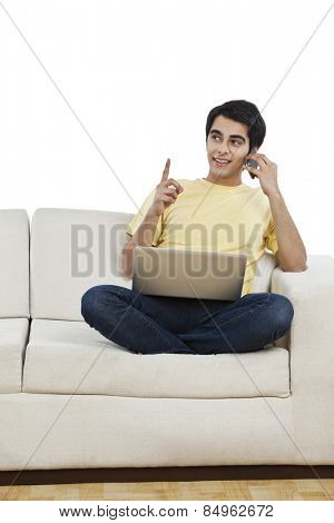 Man talking on a mobile phone and using a laptop at home