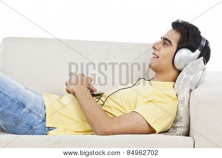 Man lying on a couch and listening to music on a mobile phone