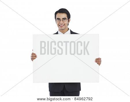 Portrait of a businessman showing a blank placard and smiling