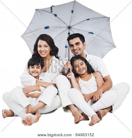 Portrait of a happy family sitting under an umbrella