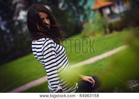 Girl In A T-shirt Is Sitting On A Rock