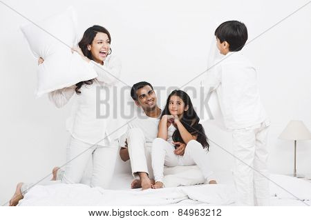 Happy family pillow fight on the bed