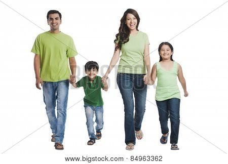 Portrait of a happy family holding hands and walking
