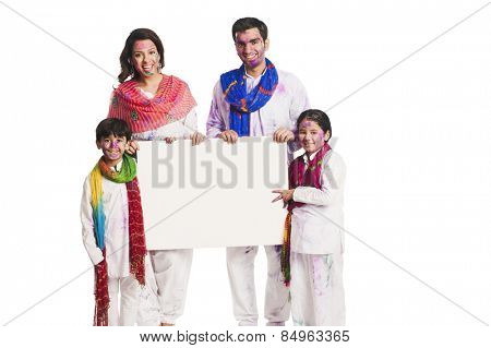 Family celebrating Holi and holding a blank placard