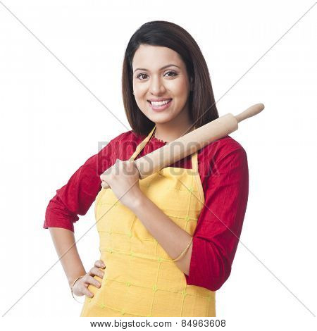 Portrait of a woman holding a rolling pin and smiling