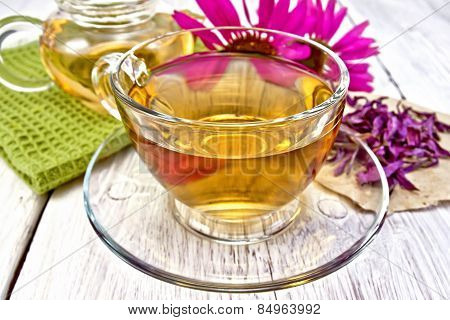Tea Echinacea in glass cup on board with napkin