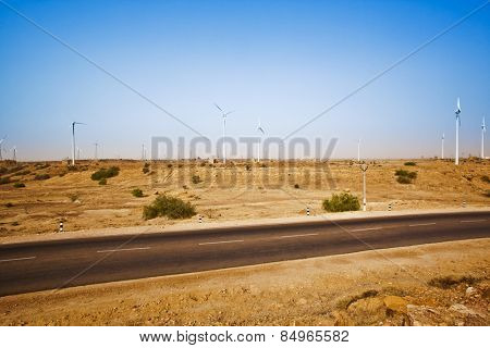 Road passing through a desert with wind turbines in distance, Jaisalmer, Rajasthan, India