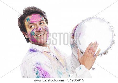 Man celebrating Holi with playing tambourine