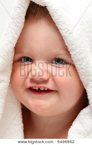 Cute baby girl smiling under a white towel after bath