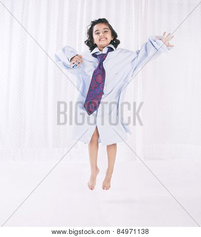 Portrait of a girl wearing oversize shirt with tie and jumping