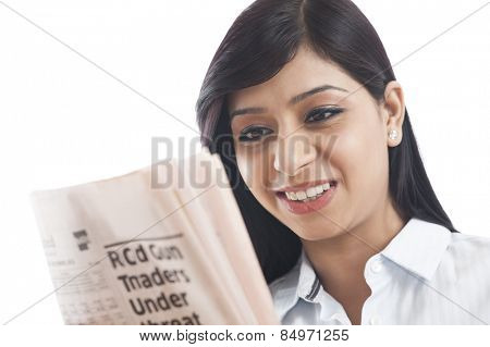 Close-up of a businesswoman reading a newspaper and smiling