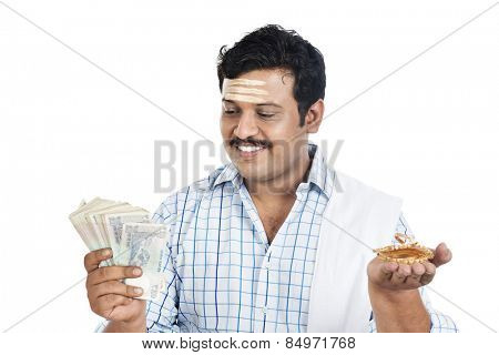 South Indian man holding money and gold bangle