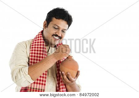 Man putting a coin into a piggy bank and smiling