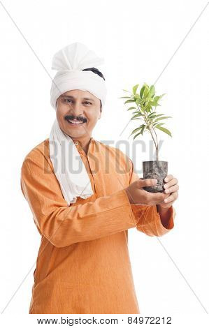 Portrait of a farmer holding a potted plant and smiling