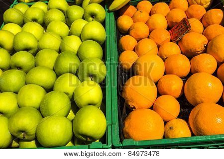 Granny smith apples and oranges in the crates for sale at a market stall, Rome, Rome Province, Lazio, Italy