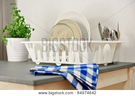 Dish drainer with plates and silverware on a table. Focus on the dish drainer