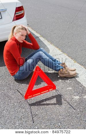 Triangle warning sign with broken down car
