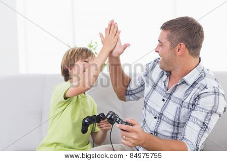 Happy father and son giving high-five while playing video game at home