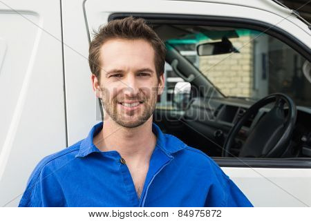 Portrait of smiling man standing in front of delivery van
