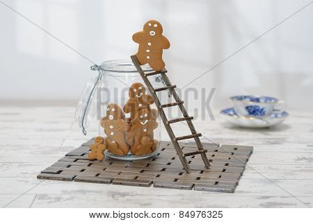 Gingerbread man at the top of a ladder about to jump into cookie jar