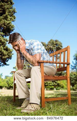 Upset man sitting on park bench on a sunny day