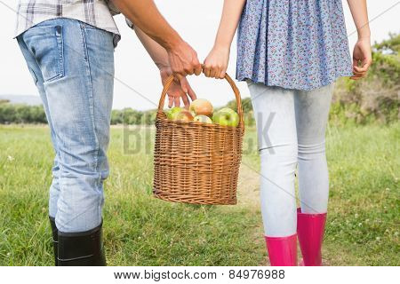 Couple holding basket full of apples on a sunny day