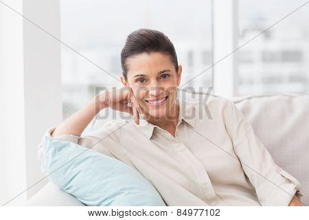 Portrait of happy woman relaxing on sofa in living room