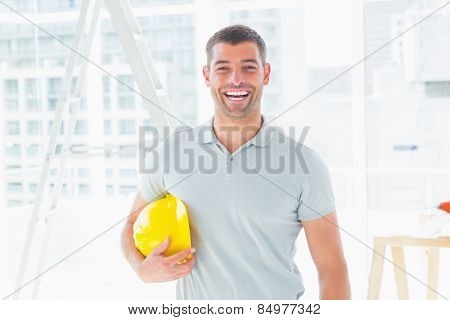 Portrait of cheerful handyman holding hardhat at construction site
