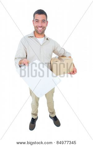 Full length portrait of happy delivery man with package giving clipboard for signature on white background