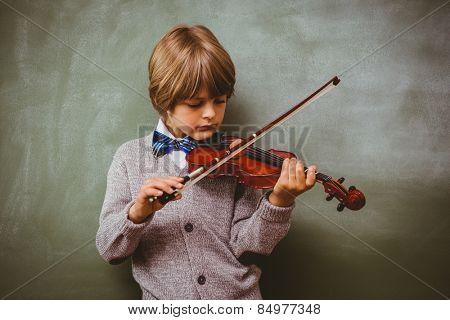 Portrait of cute little boy playing violin in classroom