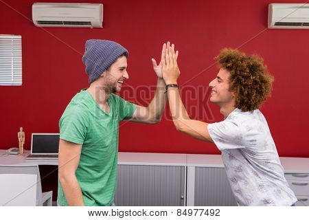Side view of two casual young businessmen high fiving in office