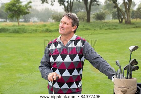 Happy golfer beside his golf bag on a sunny day at the golf course