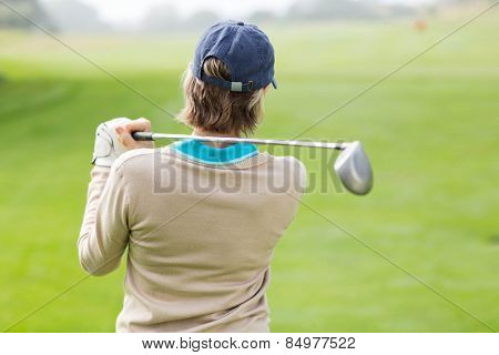 Female golfer taking a shot on a sunny day at the golf cours
