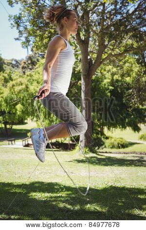 Fit woman skipping in the park on a sunny day