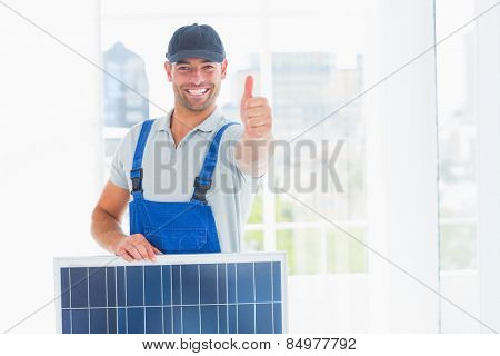 Portrait of happy workman with solar panel gesturing thumbs up in bright office