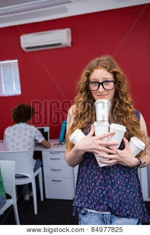 Portrait of beautiful casual businesswoman carrying disposables glasses in office