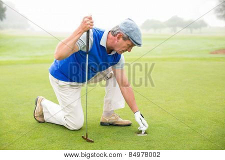 Happy golfer kneeling on the putting green on a foggy day at the golf course