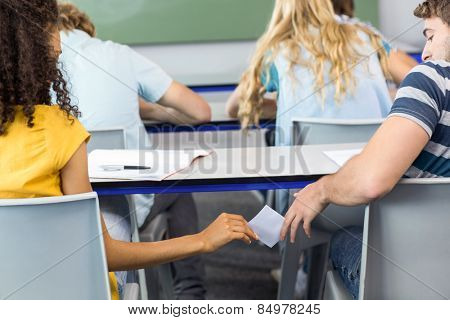 Rear view of female student passing note to friend in the classroom