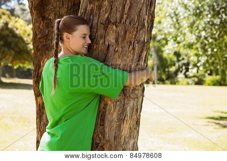 Environmental activist hugging a tree in the park on a sunny day