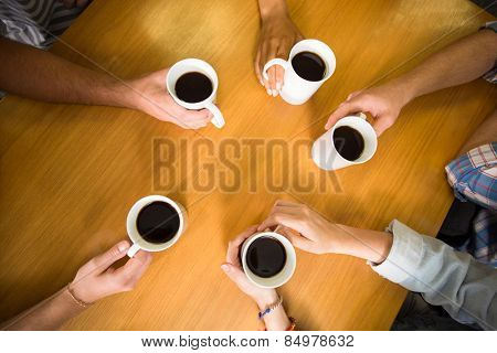 High angle view of hands holding coffee mugs on table