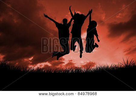 Silhouette of people jumping against red sky over grass