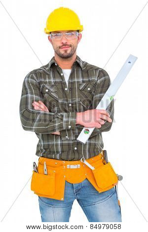 Manual worker holding spirit level with arms crossed on white background