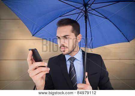 Concentrated businessman under umbrella using mobile against bleached wooden planks background