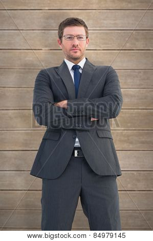 Frowning businessman looking at camera against wooden planks