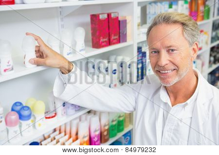 Senior pharmacist taking medicine from shelf in the pharmacy