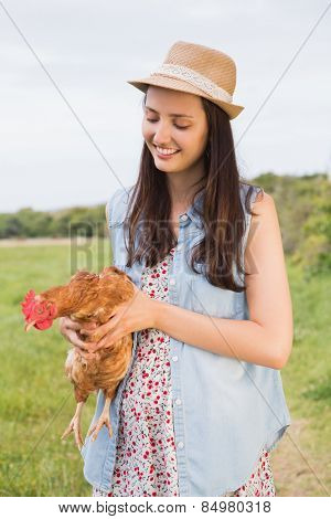 Happy brunette holding her chicken on a sunny day