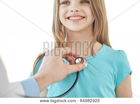 healthcare, medical exam, people, children and medicine concept - close up of happy girl and doctor hand with stethoscope listening to heartbeat