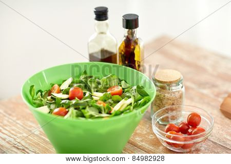 healthy eating, vegetarian food, dinner, cooking and culinary concept - close up of salad bowl and spices on kitchen table