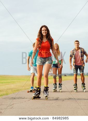 holidays, vacation, love and friendship concept - group of smiling teenagers with roller skates and skateboard riding outdoors