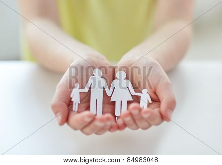 people, charity and care concept - close up of child hands holding paper family cutout at home